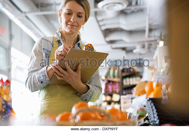 Worker with clipboard taking produce inventory in market - Stock Image