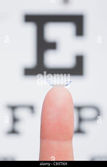 Palm with contact lens, eye chart in background, studio shot - Stock Image