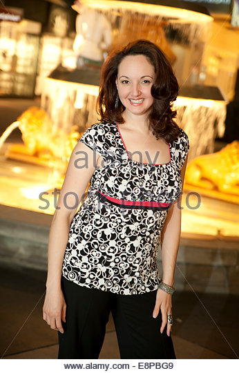 Woman standing next to fountain - Stock Image