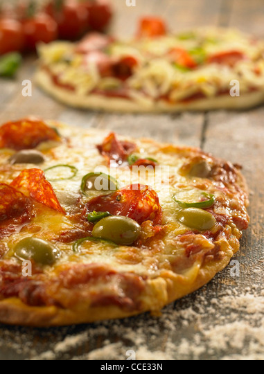 pizza on rustic wooden table top with fresh ingredients in background - Stock Image
