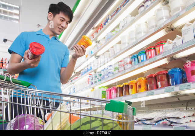 Young Man Making Decisions About Food in Supermarket - Stock Image