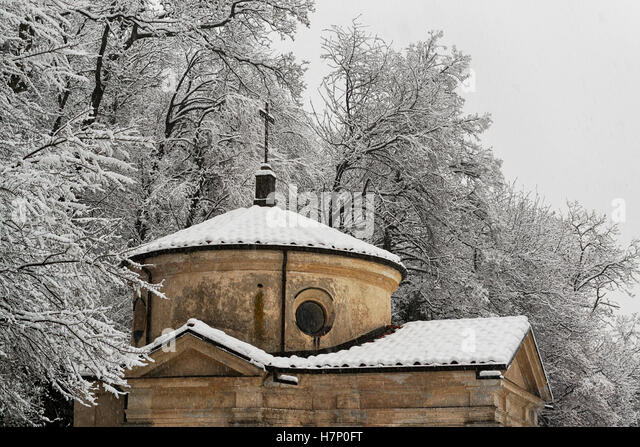 A chapel under the snow with forest background, Sacred Mount of Varese - Stock Image