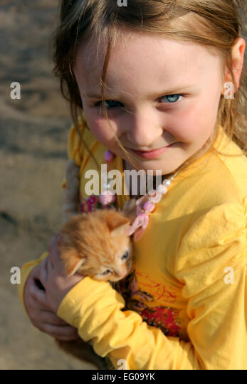 image of little girl with red kitten - Stock Image