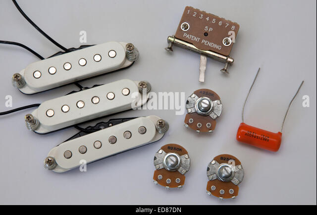 Components of an electric guitar, pick ups, volume tone controls, selector switch, capacitor, potentiometers - Stock Image