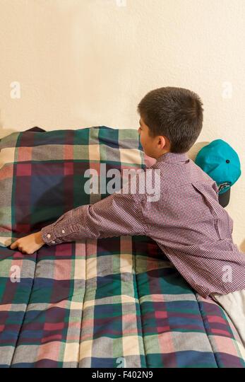 Young Korean/American boy making his bed.   MR ©Myrleen Pearson Pearson - Stock-Bilder