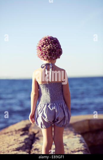 Girl in swimcap looking at the beach - Stock Image