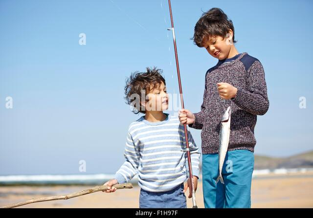 Two young boys standing together, holding fishing rod and fish - Stock Image