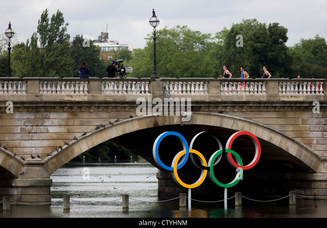 Triathletes run over Serpentine Bridge in London's Hyde Park for the Mens' Triathlon competition during - Stock Image