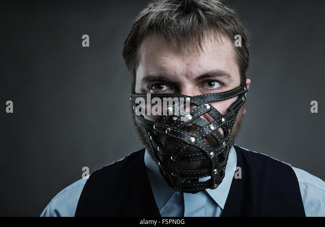 Businessman in muzzle over grey - Stock Image