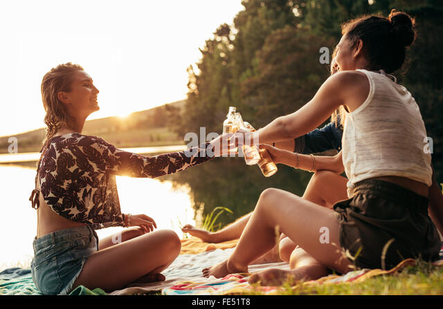 Group of young women celebrating at a lake. Young friends are toasting each other with beers during sunset at the - Stock Image