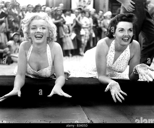 MARILYN MONROE at left and Jane Russell leave their handprints at Graumann's Chinese Theatre in Hollywood in - Stock-Bilder