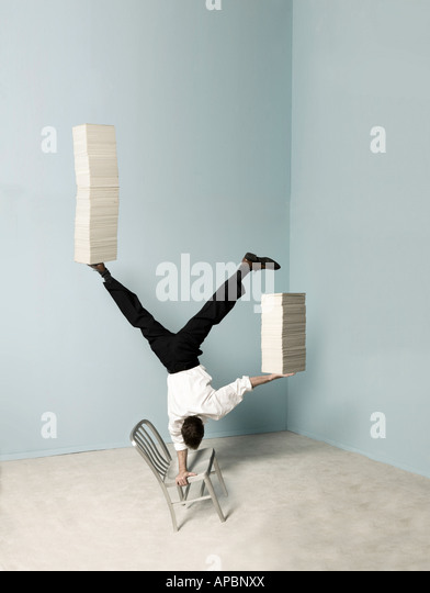 business man balances stacks of papers while doing a handstand on a chair in the office balance multi task - Stock-Bilder
