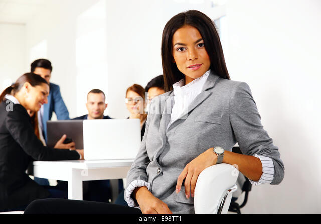 Businesswoman sitting on the office chair in front of business meeting - Stock Image
