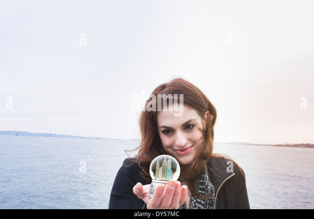 Young woman holding landmark snow globe, New York, USA - Stock-Bilder
