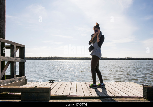 Young woman photographing with digital camera, Richmond, British Columbia, Canada - Stock Image