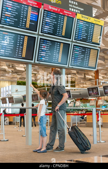 Father and daughter looking at arrival departure board in airport - Stock Image