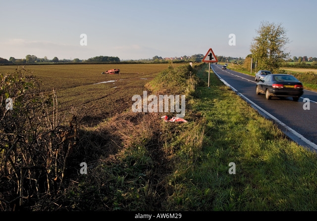 CRASHED CAR IN FIELD ALONGSIDE COUNTRY ROAD WITH TRAFFIC UK - Stock Image