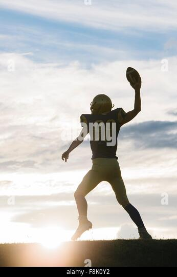 Young american football player about to throw ball - Stock Image