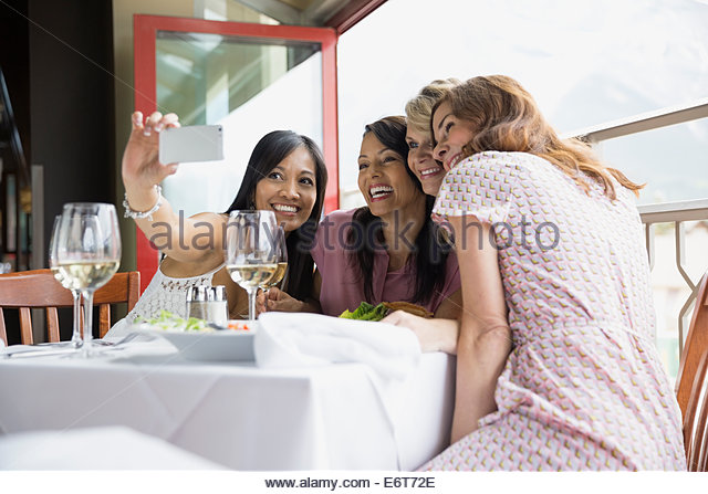 Women taking cell phone picture in restaurant - Stock Image