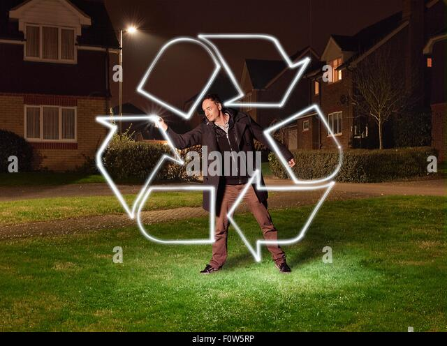 Artist light painting a recycling symbol in park - Stock Image