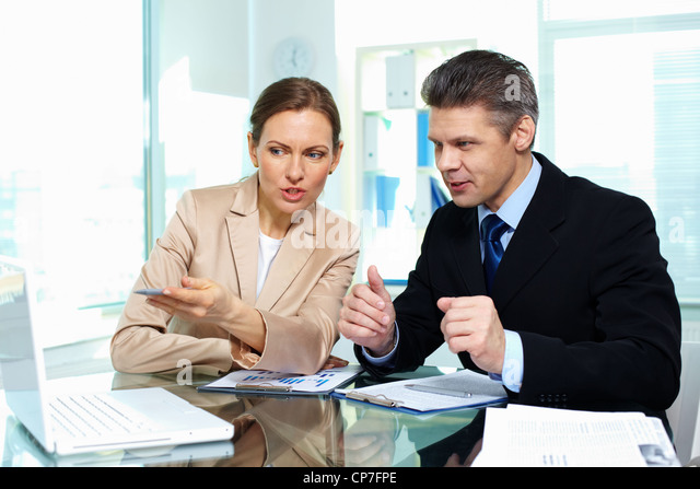 Business partners discussing possible options in terms of a new strategy - Stock Image
