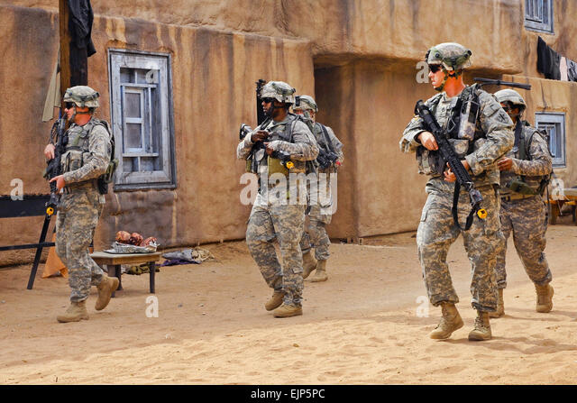 Soldiers patrol through a village during a situation training exercise at Kamal Jabour, a mock Afghan village located - Stock Image