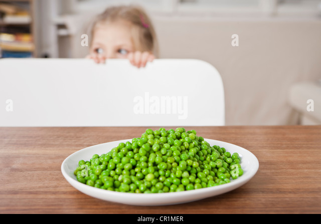 Girl hiding from peas at table - Stock Image