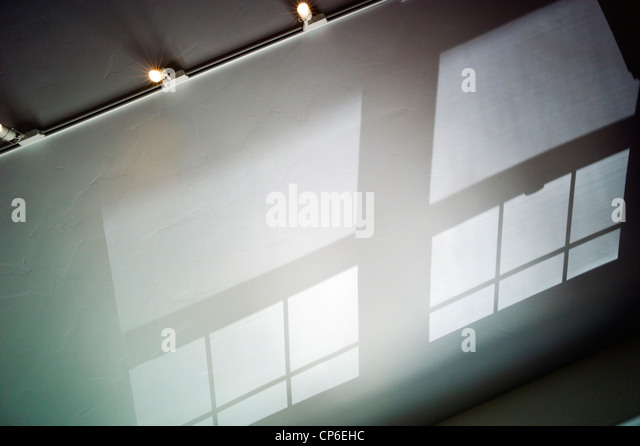 Reflections, shadows and window patterns cast on the vaulted ceiling of a home office. - Stock Image