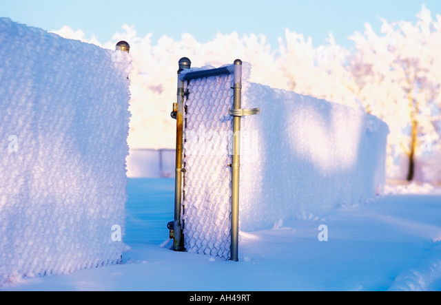 Snowy fence with gate open - Stock Image
