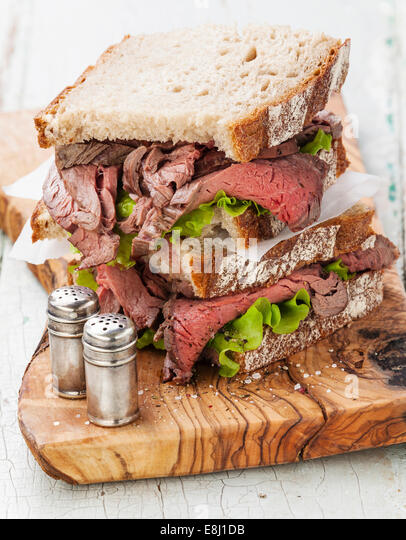Roast beef sandwiches with lettuce on olive wood cutting board - Stock Image