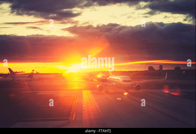 Vintage toned picture of airport at sunset, travel concept, lens flare effect. - Stock Image