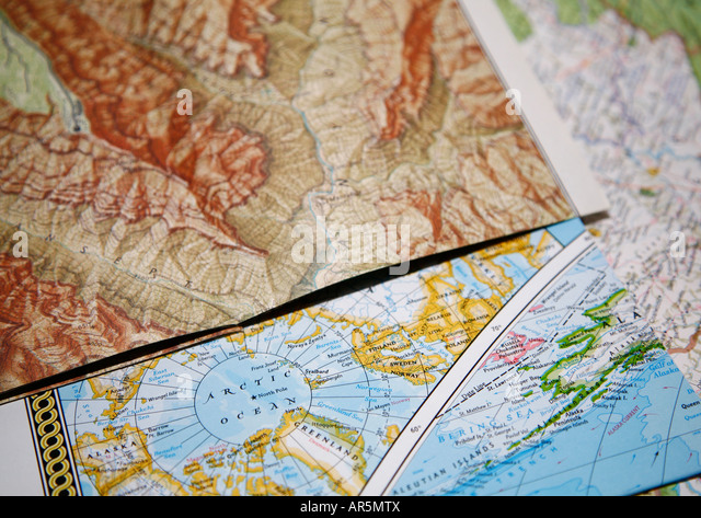 Close-up of road maps lying on top of each other Map of mountain area and map of arctic area with North Pole Shallow - Stock Image