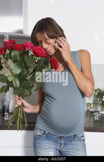 Pregnant woman using mobile phone while holding roses in kitchen - Stock Image