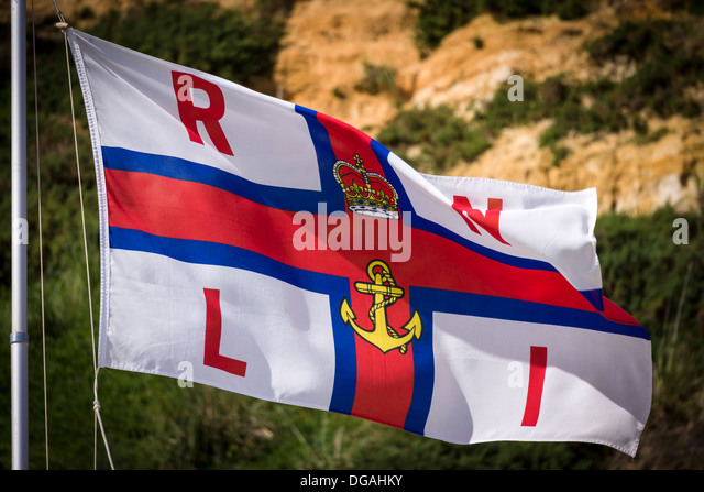 The Royal National Lifeboat (RNLI) flag flying above the beach at Bournemouth during the height of the holiday period - Stock Image