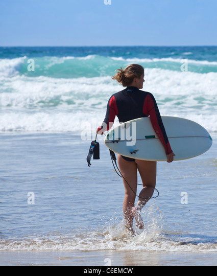 fistral beach surfer entering the water newquay Cornwall England UK GB EU England - Stock Image
