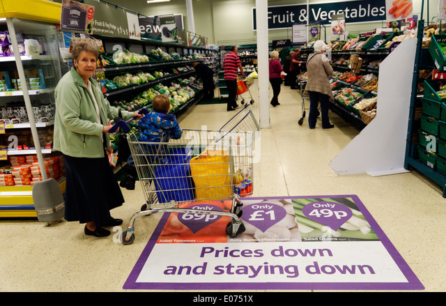 An older lady shopping in Tesco supermarket, pushing a trolley over a floor sign announcing low prices - Stock Image
