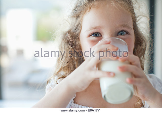 Girl drinking glass of milk - Stock Image
