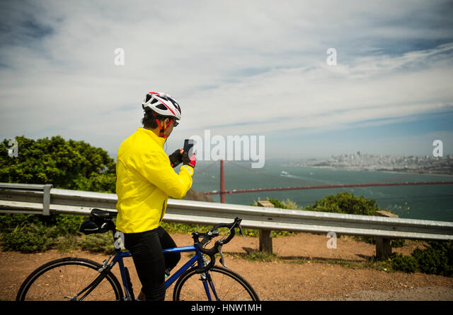 Hispanic man on bicycle photographing waterfront with cell phone - Stock-Bilder
