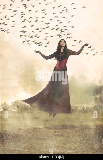 Woman floating through air with smoke and birds around her - Stock Image