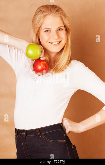young pretty blond woman choosing between red and green apple smiling - Stock Image