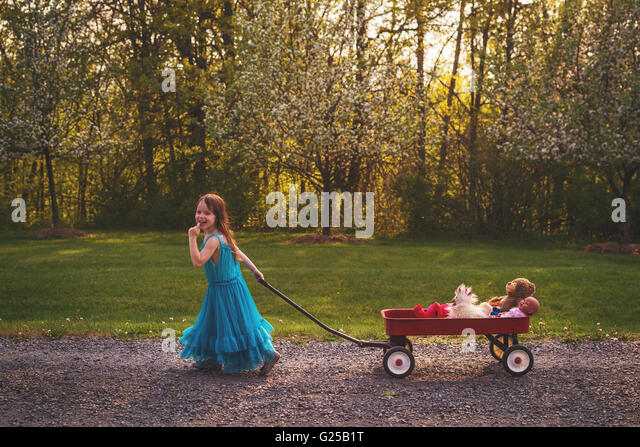 Smiling Girl in dress pulling wagon with doll and bear - Stock Image