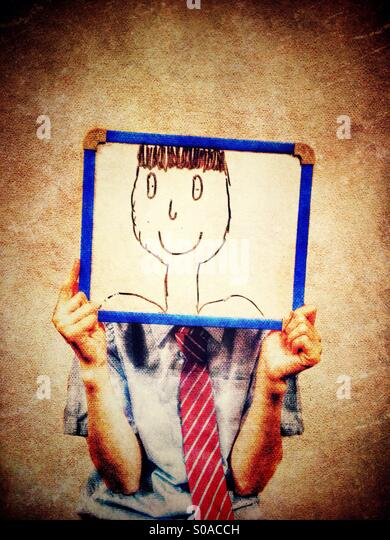 Young girl holding up white board with cartoon face in front of her face - Stock-Bilder