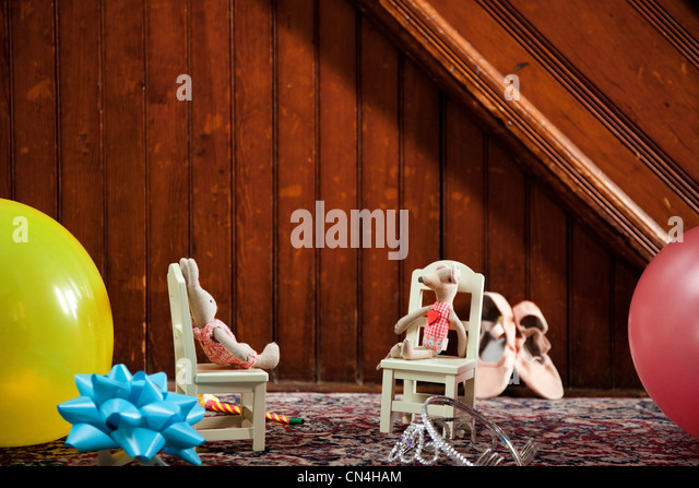 Toy animals on chairs on rug - Stock Image