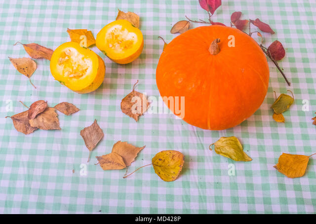 Still life of pumpkin and chopped pumpkin with autumn leaves, close-up - Stock Image