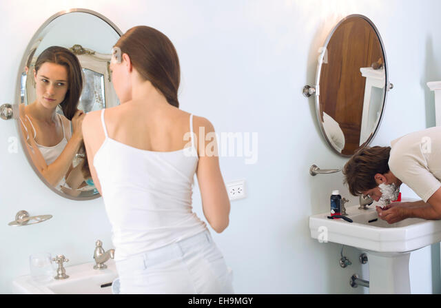 Woman brushing hair, husband shaving - Stock-Bilder