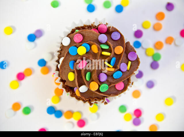 Chocolate cupcake covered with buttercream frosting and multi-colored sprinkles - Stock Image