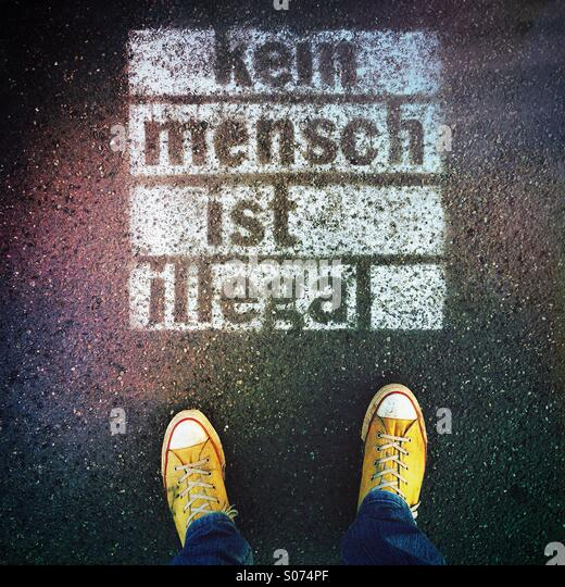 Person's feet standing next to spray-painted graffiti on sidewalk with words 'Kein Mensch ist illegal' - Stock Image