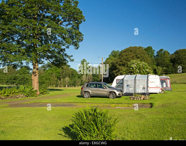Inexpensive camping site with caravan with annexe set up beside car / SUV in field with lawns & shading trees - Stock Image