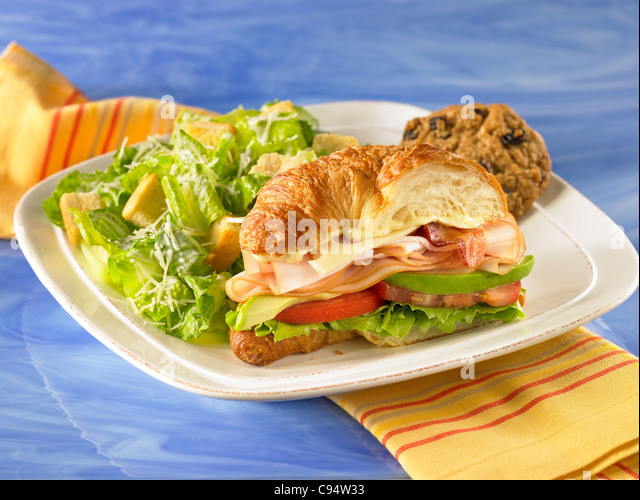Gourmet croissant club sandwich with turkey, swiss cheese, lettuce, tomato avocado and served with a side caesar - Stock Image