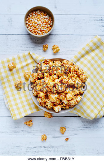 Bowl of popcorn on white rustic background with corn seeds - Stock Image